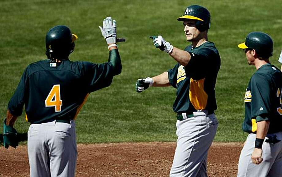 Oakland Athletics Coco Crisp left and Eric Sogard right greet Josh Willingham center, at home plate after Willingham hit a three run homer in the second inning against the Milwaukee Brewers during their spring training baseball game at Maryvale Baseball Park in Phoenix, Ariz. Thursday, March 1, 2011. Photo: Lance Iversen, The Chronicle