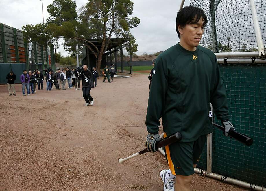 Hideki Matsui, followed by a large group of journalists, heads back to the clubhouse after hitting at Phoenix Stadium on Sunday, Rain kept many of the players off the field, but new designated hitter Matsui took some swings in the batting cage area, much to the delight of the Japanese media. Photo: Brant Ward, The Chronicle