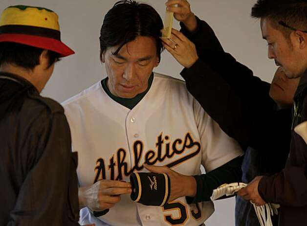 Hideki Matsui talks with a photographer as he prepares for his photo shoot at the Papago Park training facility for the Oakland A's on Saturday. Photo: Brant Ward, The Chronicle