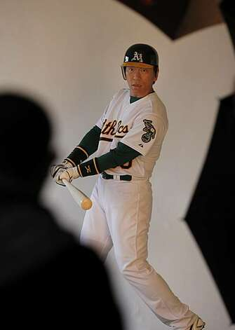 Hideki Matsui asks a photographer how he should swing for the camera at the Papago Park training facility for the Oakland A's on Saturday. Photo: Brant Ward, The Chronicle