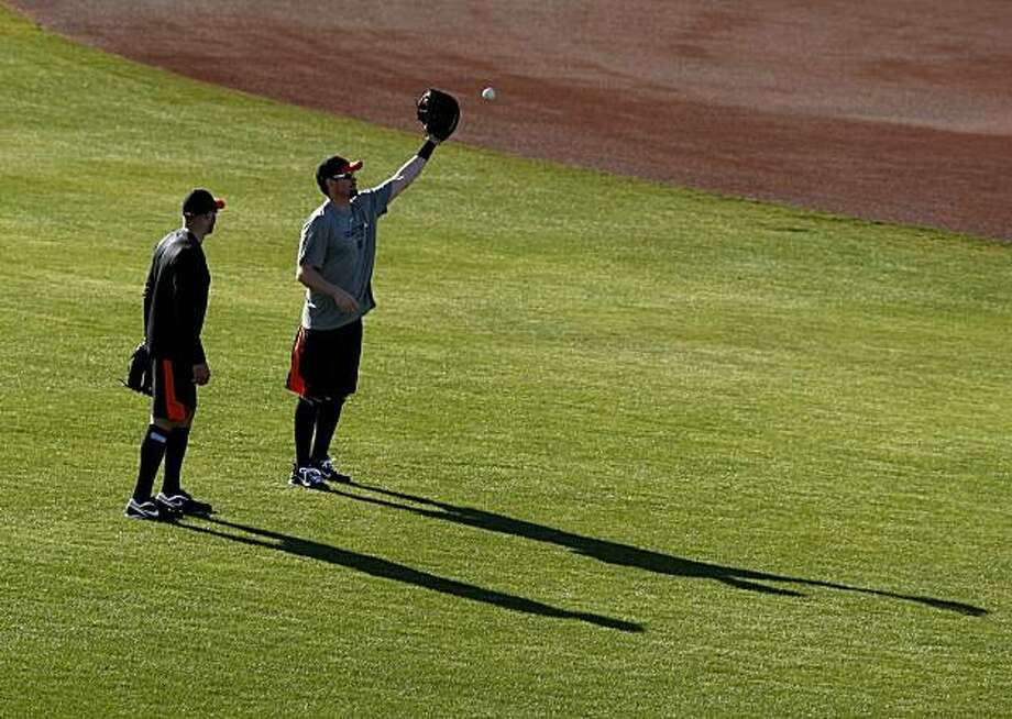 Nate Schierholtz (left) and Aubrey Huff had a field to themselves as they played catch. The San Francisco Giants held their second workout of the spring training season at Scottsdale Stadium in Arizona Wednesday February 16, 2011. Photo: Brant Ward, The Chronicle