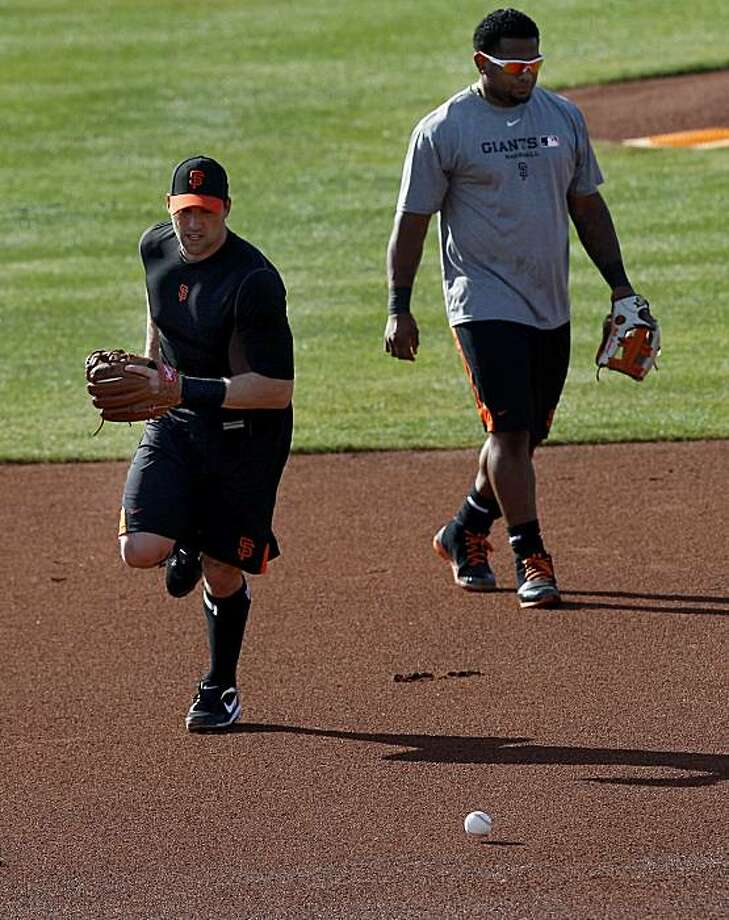 Mark DeRosa (left) and Pablo Sandoval took some grounders at third base. The San Francisco Giants held their second workout of the spring training season at Scottsdale Stadium in Arizona Wednesday February 16, 2011. Photo: Brant Ward, The Chronicle