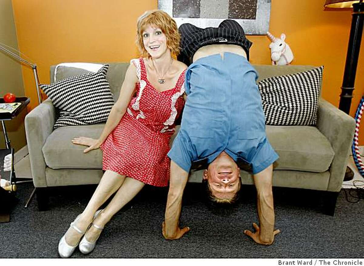 Aaron does a yoga position on their favorite couch for his favorite girl. Aaron Hale and Laura Camp met while Camp was a yoga teacher in late 2005. They are together at the couple's home in Emeryville, CA.