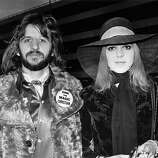 "3rd February 1970: British pop star Ringo Starr with his first wife Maureen (1946 - 1994) at an airport. Ringo's badge refers to the film ""The Magic Christian"" in which he starred along with Peter Sellers."