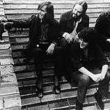 Promotional portrait of American rock group Quicksilver Messenger Service as they sit on a roof and pet a cat, 1970s. Left to right, the band is British keyboardist Nicky Hopkins (1944 - 1994), American drummer Greg Elmore (with beard), American guitarist John Cipollina (1943 - 1989), and American bass player David Freiberg. (Photo by Capitol Records/Courtesy of Getty Images).