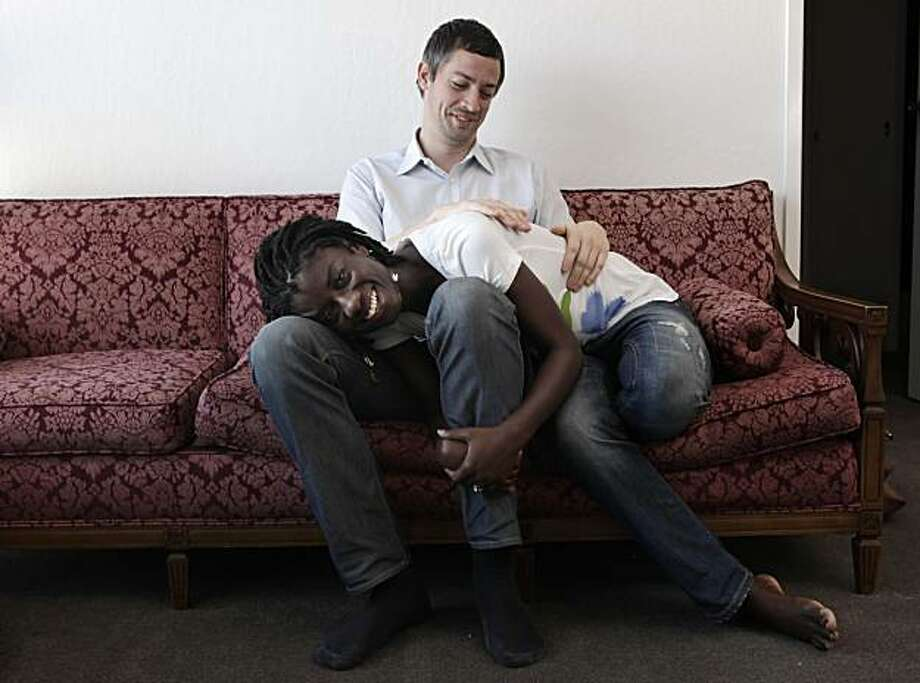 Caleb and Akua Bashor cuddle on their couch at home, Friday May 14, 2010, in San Francisco, Calif. The couple have been together for seven years. Photo: Lacy Atkins, The Chronicle