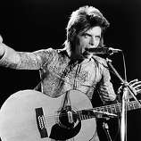 "British rock singer David Bowie performs with an acoustic guitar on stage, in costume as ""Ziggy Stardust,"" circa 1973."