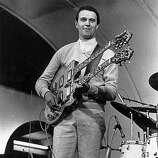 1974: The English jazz-rock guitarist John McLaughlin playing a double-necked guitar in performance with his band The Mahavishnu Orchestra.
