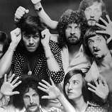 A portrait of the British rock band Electric Light Orchestra with their faces and hands pressed up against glass, circa 1975.