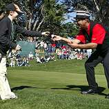 Rebecca Thompson, 12, of San Francisco reaches for a golf ball from comedian George Lopez, who lured her out of the galley to get her autographed prize in the third round of the AT&T Pebble Beach National Pro-Am on Saturday.