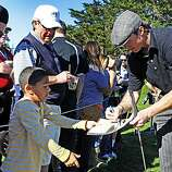 Gavin Carlson, 8, of Redwood City gets an autograph from Saints quarterback Drew Brees during third round action at the AT&T Pebble Beach National Pro-Am on Saturday.