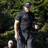 Phil Mickelson reacts to a birdie putt on the third hole in the third round of the AT&T Pebble Beach National Pro-Am on Saturday.