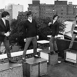 Mick Avory, Ray Davies, Dave Davies and Pete Quaife of the British rock band the Kinks standing on a London rooftop..