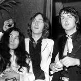 18th July 1968:  Beatle John Lennon (1940 - 1980) and his Japanese girlfriend Yoko Ono with Beatle Paul McCartney, right, at the premiere of the new Beatles film 'Yellow Submarine' at the London Pavilion. John and Paul hold apples, the symbol of their newly formed company, Apple Corps. Thousands of Beatle fans brought traffic to a standstill in Piccadilly Circus as they waited to see the group arrive at the premiere.  (Photo by Michael Webb/Keystone/Getty Images)