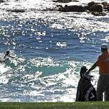 J. B. Holmes and his caddie watch a surfer off Carmel Beach as the wait for the 9th green to clear during opening rounds of the annual AT&T National Pro-Am golf tournament Thursday, Feb. 10, 2011, in Pebble Beach, Calif.