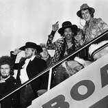 1968: Jimi Hendrix and Mitch Mitchell of The Jimi Hendrix Experience wave goodbye as they board an aeroplane at London Airport, with assorted members of the Byrds, the Soft Machine and the Alan Price Set..