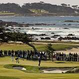 Phil Mickelson bends over to mark his ball on the par-3 11th hole at the Monterey Peninsula course during round 1 action of the AT&T Pebble Beach National Pro-Am in Pebble Beach, Ca. on Thursday Feb. 10, 2011.