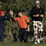 Matt Bettencourt, (left) high fives his partner, Matt Cain after his shot on the par-3 3rd hole of the Monterey Peninsula course, as John Daly walks off the tee, during round 1 action of the AT&T Pebble Beach National Pro-Am in Pebble Beach, Ca. on Thursday Feb. 10, 2011.