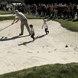 Actor, Kevin Costner, tries to rake the greenside bunker, at the 1st hole at Pebble Beach, as his son's, Hayes, 2-years-old,  (center) and Cayden, 3-years old, run around in the sand during the Celebrity Challenge on on Wednesday Feb. 9, 2011, a day before the start of the AT&T Pebble Beach National Pro-Am in Pebble Beach, Ca.