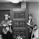 "Group portrait of the American psychedelic rock and roll band ""The Electric Prunes"" as they pose around a loose wood panel, mid to late 1960s. Clockwise from left, American guitarist and co-founder James Lowe, bassist and co-founder Mark Tulin, guitarist Mike Gannon (? - 1970), lead guitarist and co-founder Ken Williams, and drummer Quint (Michael Fortune). James Lowe lifts up his shirt to reveal his stomach while Mark Tulin and Mike Gannon hide behind the door. The band lineup changed several times during its existance until its split in 1970.."