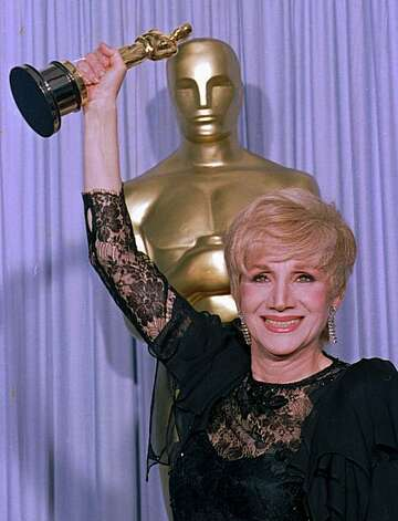 "Olympia Dukakis holds her Oscar high April 11, 1988, as she stands backstage at the Shrine Auditorium in Los Angles after being honored at the 60th Academy Awards as best supporting actress for her role in ""Moonstrck."" (AP photo/Lennox Mcleondon/stf) Photo: Lennox Mclendon"