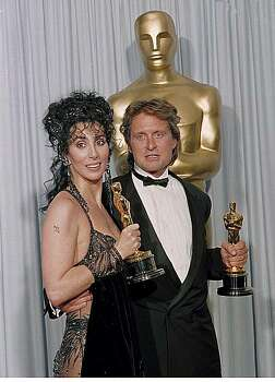 "Cher and Michael Douglas, right, pose with their Oscar statuettes backstage at the 60th Annual Academy Awards at the Shrine Auditorium in Los Angeles, Ca., April 11, 1988.  Cher won the best actress award for her role in ""Moonstruck.""  Douglas won the best actor award for his role in ""Wall Street.""  (AP Photo/Lennox McLendon) Photo: Lennox Mclendon"