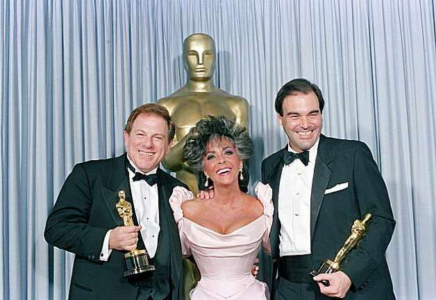 "Elizabeth Taylor is flanked by Oscar-winners Arnold Kopelman, left, and Oliver Stone backstage at the 1986 Academy Awards at the Dorothy Chandler Pavilion in Los Angeles, Ca., March 31, 1987.  Stone won the award for best direction for ""Platoon,"" which won best picture presented to producer Kopelman.  (AP Photo/Lennox McLendon) Photo: Lennox Mclendon"