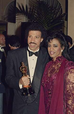 Singer Lionel Richie, left, stands with his wife Brenda as he holds the Oscar he won at the Academy award show  in Los Angeles on March 23, 1986.  (AP Photo) Photo: Anonymous