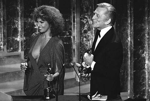 Actress Raquel Welch, left, holds the Oscar she is about to present for the Best Achievement in Documentary Films Monday, April 4, 1978  at the 50th Annual Academy Awards in Los Angeles. At right is actor Kirk Douglas. (AP Photo) Photo: Anonymous