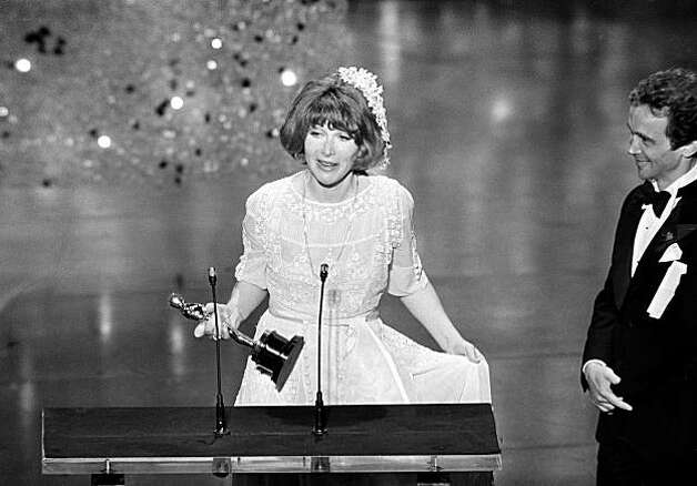 "Lee Grant accepts the Oscar awarded to her as best supporting actress for her role in ""Shampoo,"" at the annual Academy Awards, on March 29, 1976, in Los Angeles, California. She explains to the audience she wore a wedding dress because she wanted a bride's luck. (AP Photo)"