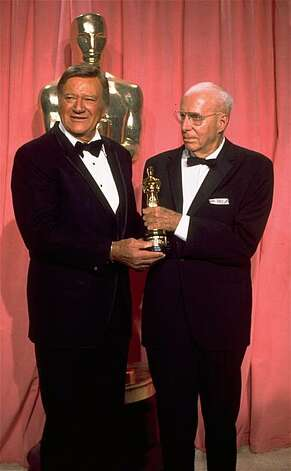 John Wayne, left, presents a special Oscar award to veteran film director Howard Hawks during the 47th Annual Academy Awards ceremony on April 9, 1975 at the L.A. Music Center.  (AP Photo)