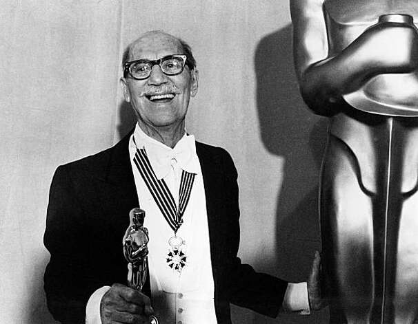 Groucho Marx displays his Honorary Oscar for Lifetime Achievement at the Academy Awards presentation in Los Angeles, Ca., April 3, 1974.  Groucho is wearing the Commander of Arts and Letters medal he received from the French government at Cannes in 1972.  (AP Photo)