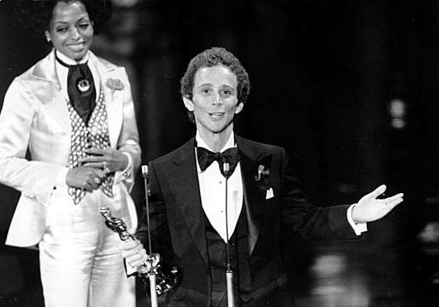 "Joel Grey gestures as he thanks the Motion Picture Academy for the Oscar he won at the 45th Annual Academy Awards in Hollywood, Ca., on March 27, 1973.  Grey won for best supporting actor for his role in ""Cabaret.""   Behind him is best actress nominee Diana Ross, who presented the award.  (AP Photo)"