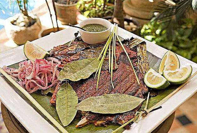 Pescado tikin-xic is an ancient recipe for fresh whole fish marinated in a sauce of achiote and Seville oranges, wrapped in a banana leaf and cooked on a grill. Photo: Eduardo Cervantes, Los Dos
