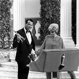 "Walter Matthau accepts his Oscar from presenter Shelley Winters on stage during the Academy Awards ceremony at the Santa Monica Civic Auditorium, Ca., April 10, 1967.  Matthau won best supporting actor for his role in ""The Fortune Cookie.""  Matthau's arm is in a cast from an injury in a bicycle accident.  (AP Photo)"