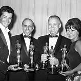 "Oscar winners for ""The West Side Story,"" George Chakiris, left, Jerome Robbins, Robert Wise and Rita Moreno, pose at the Academy Awards in Santa Monica on April 9, 1962.  Chakiris won best supporting actor; Robbins won best director; Wise won as co-director with Robbins and as producer of best picture; and Moreno won best supporting actress.  (AP Photo)"