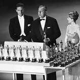 "French actor and director Jacques Tati accepts his Oscar for best foreign language picture, awarded to him for the film ""Mon Oncle"" (My Uncle) in Hollywood, Calif., on April 1, 1959. The presenters are actor Robert Stack and dancer Cyd Charisse. (AP Photo)"