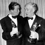 "As the first father-son team to win the Academy Awards in the same year, John Huston, left, and Walter Huston pose with their Oscars at the annual Academy Awards presentation in Hollywood, on March 24, 1949. John Huston won best screenplay and best director for the motion picture ""Treasure of the Sierra Madre""; father Walter's performance as Howard in the same movie earned him the Oscar for best supporting actor. (AP Photo)"