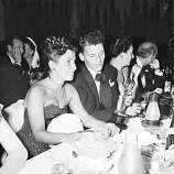 "At a crowded table at Ciro's, Frank Sinatra steals a glance at his Oscar March 11, 1946, which he won for his performance in the picture ""The House I Live In"".  His wife Nancy looks on at left.  (AP Photo)"