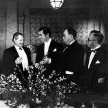 "Clark Gable shows his Oscar for ""It Happened One Night"" to Lionel Barrymore, far left, presented at the 1934 Academy Awards banquet at the Biltmore Hotel in Los Angeles, Ca., Feb. 27, 1935.  Humorist Irving S. Cobb, who presented the award, is at right.  The man at far right is not identified.  (AP Photo)"