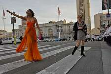 Cristina Robinson, left waves to the traffic as they wait for her to cross the street after being photographed by Aubrie Pick, in front of the valet at San Francisco City Hall, Wednesday January 26, 2011, in San Francisco,Calif.  Robinson was among the crowd that gathered for a dinner to celebrate the opening of the San Francisco Ballet season.