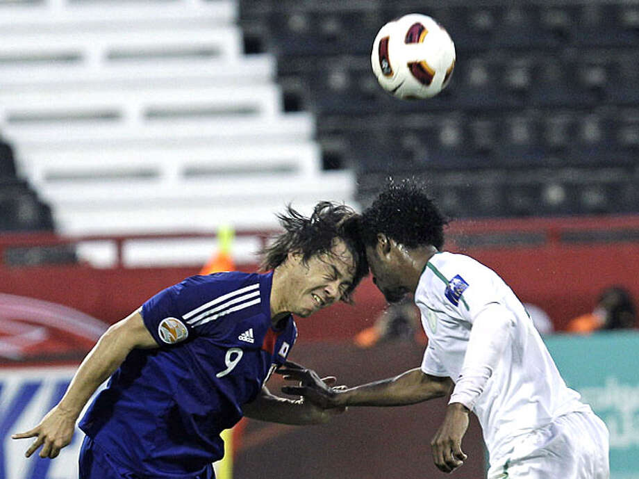 Japan's player Shinji Okazaki, left, and Saudi Arabia's player Kamil Al Mousa, right, clash heads as they fight for the ball, during their AFC Asian Cup group  B soccer match at Al-Rayyan Stadium, in Doha, Qatar, Monday Jan. 17, 2011. Photo: Hussein Malla, AP