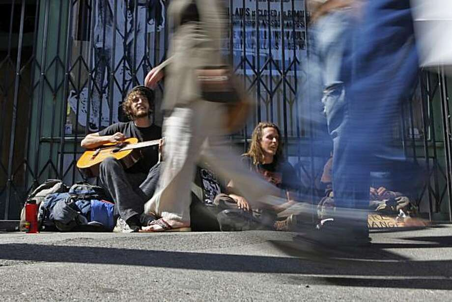 "Peter Barker, 24, left, Michael Cook, 23, and  Aarron West, 22, sit on the sidewalk along Haight Street, Saturday May 22, 2010, in San Francisco, Calif. All three have been living on the street for less an one month and love it. "" The sidewalks belong to the people,"" says Barker, when ask about the Mayors legislation banning people from sitting on the sidewalks. Photo: Lacy Atkins, The Chronicle"