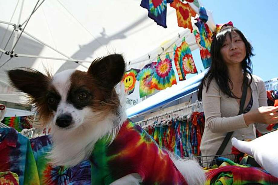 Bruno displays a tie-dye shirt from the booth of Angeline Shi (right) and her family at the Haight Street Fair on Sunday. Photo: John Sebastian Russo, The Chronicle