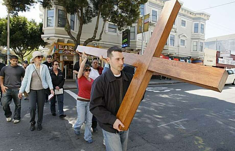 Forrest Higgins leads a small procession from St. Agnus Catholic Church through the Haight Ashsbury neighborhood in San Francisco, Calif.,  carrying a large wooden cross to observe Good Friday on March 20, 2008. The group stopped along the way to recite the Stations of the Cross to remember the death of Jesus Christ.  Photo by Michael Macor/ San Francisco Chronicle Photo: Michael Macor, The Chronicle