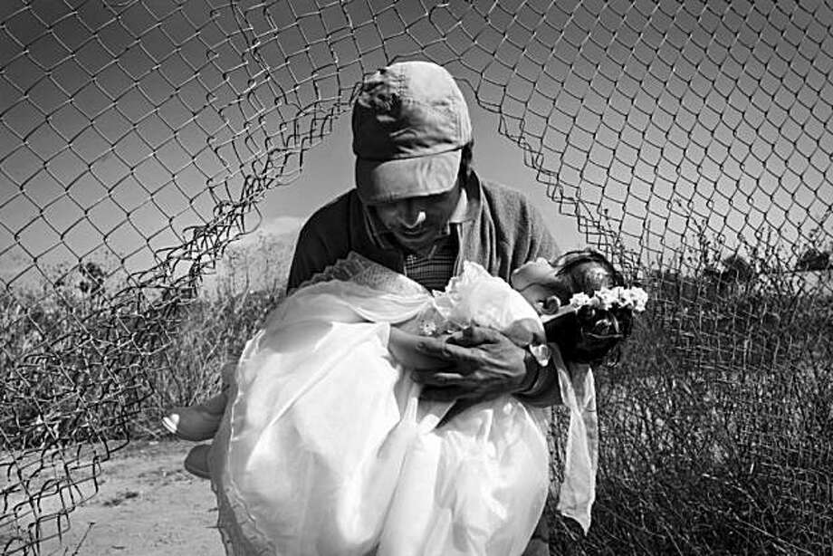 Antonio Hernandez carries his daughter Angela to her baptism ceremony in Guadalajara where they live rent free in exchange for making bricks. Photo: Josh Meltzer, Photo Philanthropy