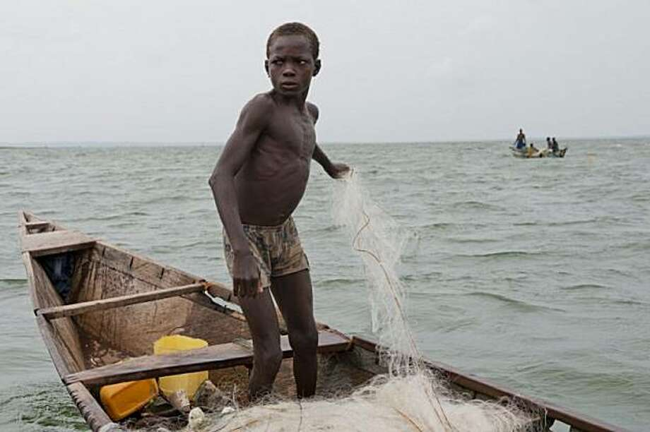 An adolescent boy pulls in nets after detangling them from the tree stumps below the water. Many children drown during this task. Photo: Nancy Borowick, Photo Philanthropy