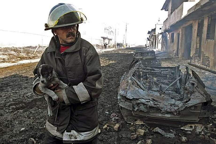 A firefighter carries a puppy after an oil pipeline explosion in the town of San Martin Texmelucan, Mexico, Sunday Dec. 19, 2010.  An oil pipeline operated by Mexico's state-owned oil company Petroleos Mexicanos, or Pemex, exploded early Sunday when thieves were attempting to steal oil, killing at least 27 people, injuring at least 52 people and scorching more than 115 homes, authorities said. Photo: Rodolfo Perez, AP