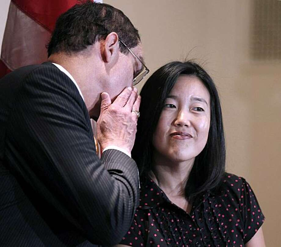 DC Schools Chancellor Michelle Rhee, right, listen to DC City Council chairman and Democratic Mayoral candidate Vincent Gray, left, whisper in her ear during an announcement that she is resigning, Wednesday, Oct. 13, 2010, in Washington. Photo: Pablo Martinez Monsivais, AP
