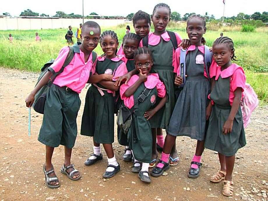 Schoolgirls stop to pose on the way home from school in Monrovia. Photo: John Diaz, The Chronicle